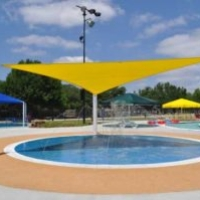Splash Pad - The Splash Pad is covered by a yellow triangular shade canopy to keep the sun off the kids as they play in the numerous ground sprayers.